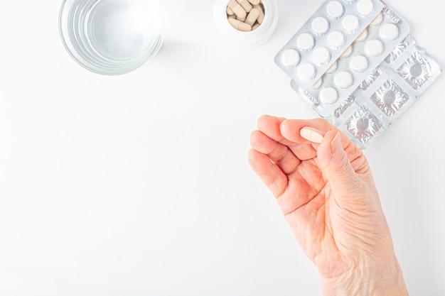 Mão feminina idosa segurar uma pílula de cálcio. cuidados médicos e médicos para idosos. medicamentos para o tratamento da osteoporose em idosos