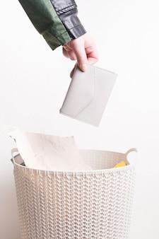 Mão feminina jogando bolsa em uma lata de lixo