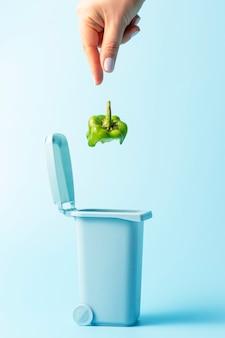Mão feminina jogando lixo de comida na lata de lixo