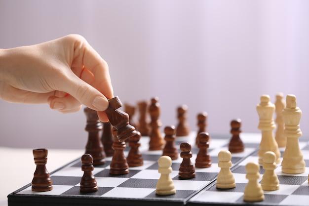 Mão feminina jogando xadrez na luz desfocada
