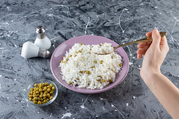 Mão feminina levando arroz delicioso com garfo em fundo de mármore.