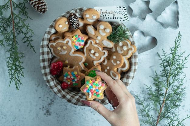 Mão feminina levando biscoito de natal da cesta.
