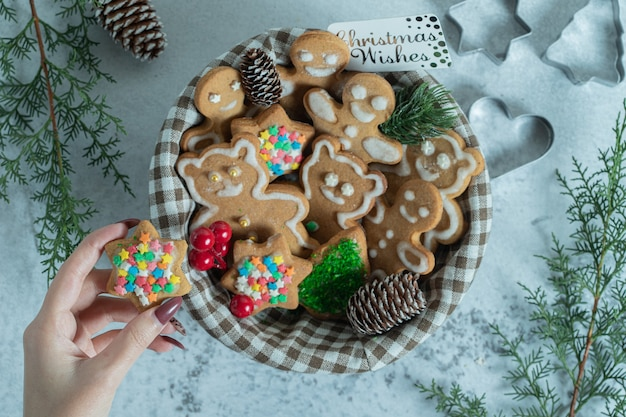 Mão feminina levando biscoito estrela da cesta sobre o branco.