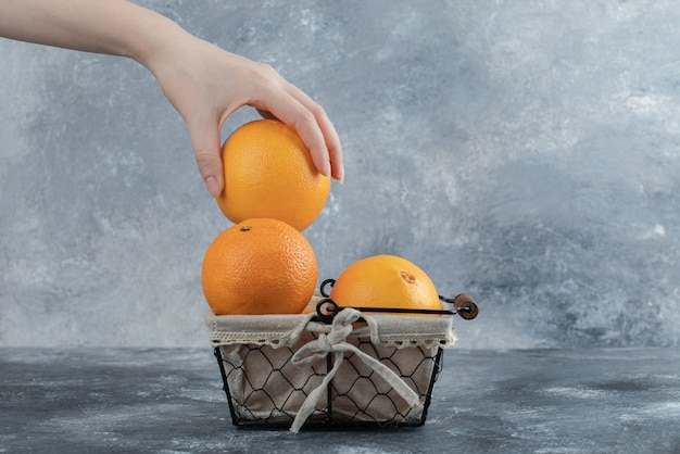 Mão feminina levando laranja da cesta.