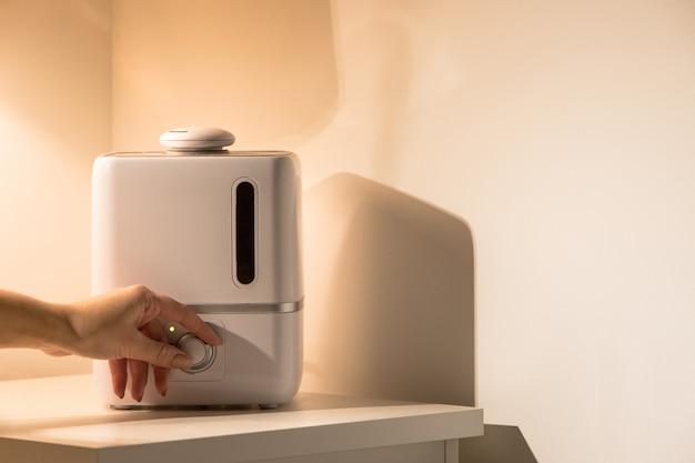 Mão feminina ligar difusor de óleo de aroma na mesa de cabeceira à noite em casa, vapor do umidificador de ar