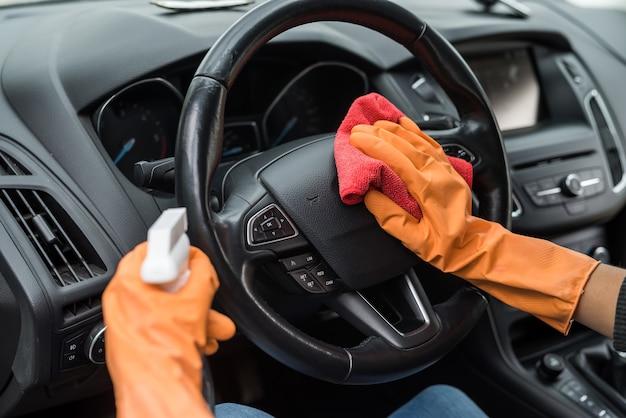 Mão feminina limpando o interior do carro contra coronavírus e pandemia com fluido desinfetante para lavagem de véquil