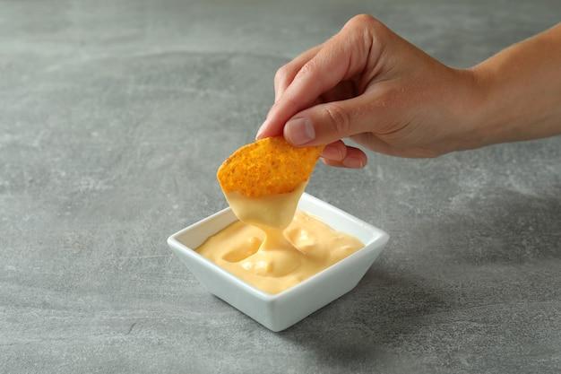 Mão feminina mergulhando batata frita em molho de queijo, close-up