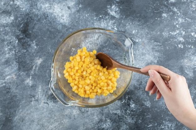 Mão feminina, misturando grãos doces em uma tigela de vidro.