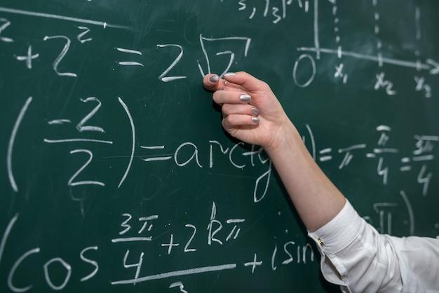 Mão feminina mostrando a fórmula matemática no quadro-negro. de volta à escola. educação offline