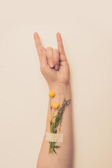 Mão feminina mostrando gesto de chifres com flores no pulso