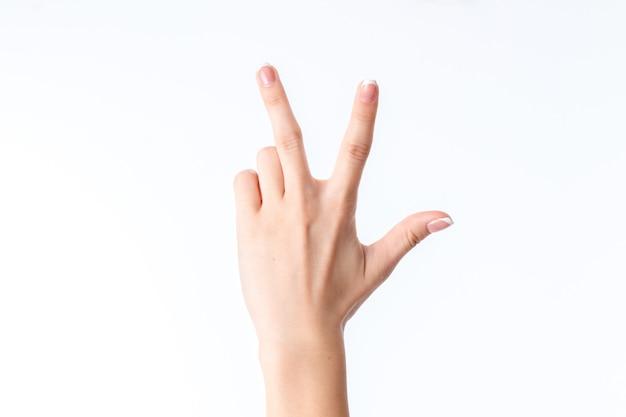 Mão feminina mostrando o gesto com close de três dedos