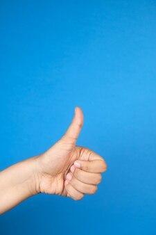 Mão feminina mostrando um polegar para cima sobre fundo azul
