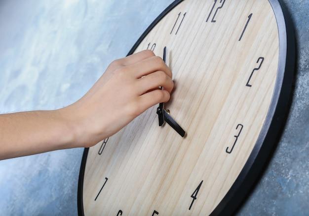 Mão feminina muda o tempo em um grande relógio de parede