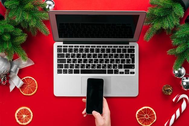 Mão feminina mulher que trabalha em uma mesa de escritório com decorações festivas de natal