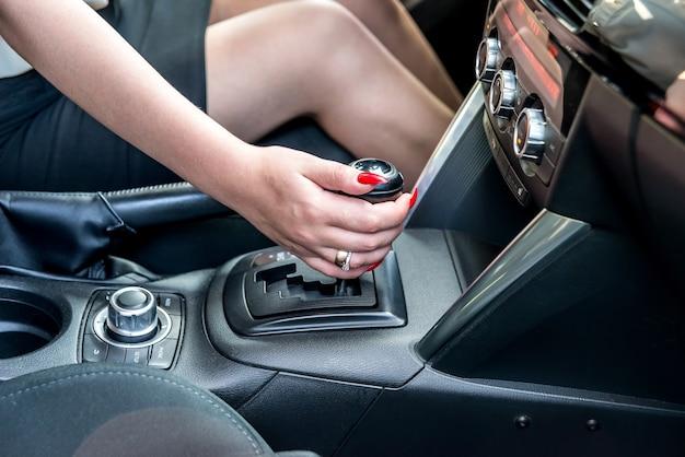 Mão feminina na alavanca da transmissão automática, close-up