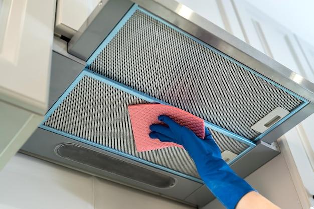 Mão feminina na capa protetora de borracha ã'â inclinada com pano na cozinha.