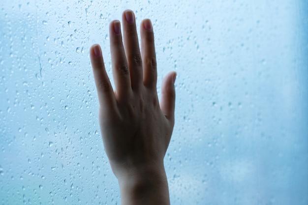 Mão feminina na janela durante a chuva. copo em gotas de água.
