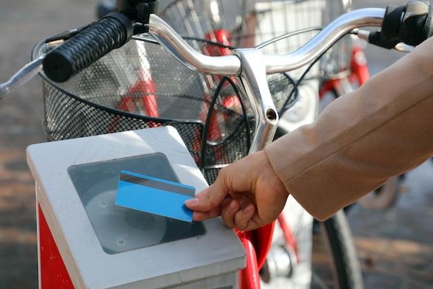 Mão feminina pagando bicicleta com cartão de crédito, usando moderno sistema sem contato em estação de aluguel ao ar livre