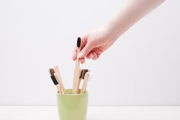 Mão feminina pega uma escova de dentes de bambu do copo