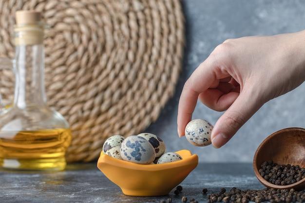 Mão feminina pegando ovo de codorna da tigela