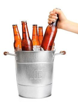 Mão feminina pegando uma garrafa de vidro de cerveja em um balde de metal isolado no branco