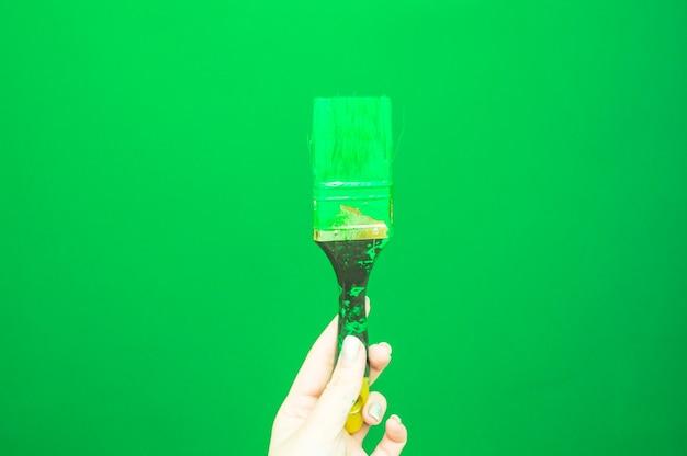 Mão feminina pinta a parede com pincel. renovando com tinta de cor verde. copie o espaço
