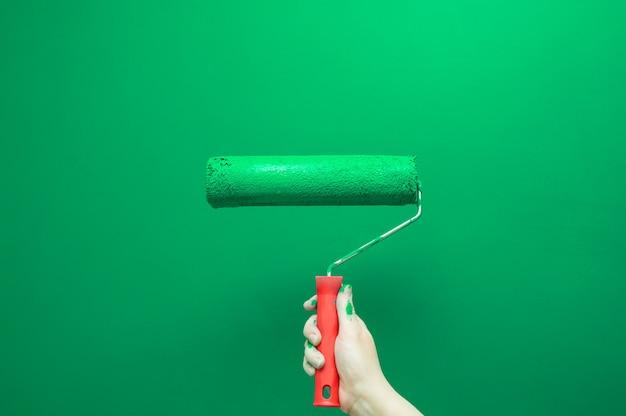 Mão feminina pinta a parede com rolo de pintura. renovando com tinta de cor verde