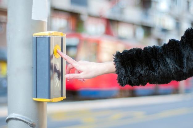 Mão feminina pressionando botão para o semáforo. use semáforos na encruzilhada. o botão do mecanismo ilumina os semáforos na rua. controle do sistema de interseção do semáforo próximo.