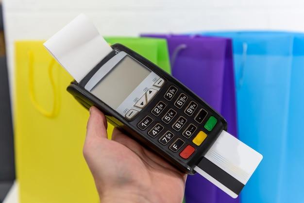 Mão feminina pressionando botões no terminal com cartão