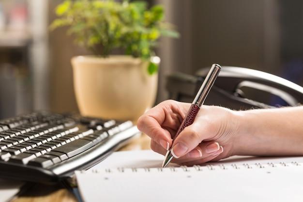 Mão feminina redigindo relatório no local de trabalho