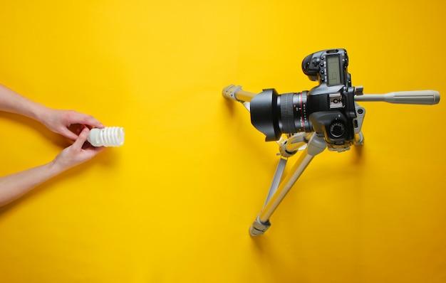 Mão feminina rever eco espiral lâmpada com câmera no tripé. vista do topo. minimalismo