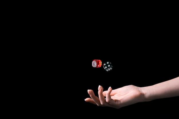Mão feminina rolando dados isolados em fundo preto