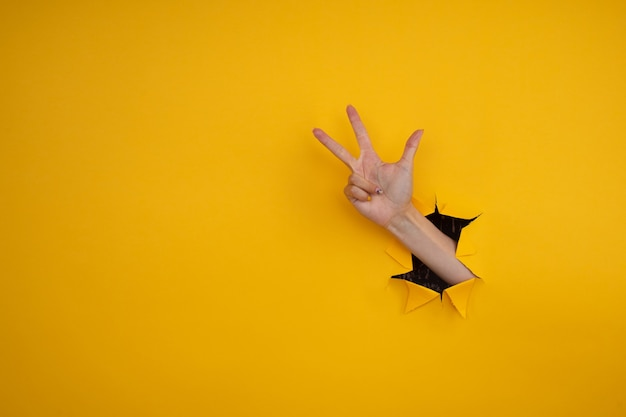 Mão feminina sai do buraco no papel, sobre um fundo amarelo. sinal de três dedos, copie o espaço.