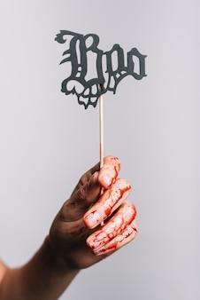 Mão feminina sangrenta segurando sinal de boo