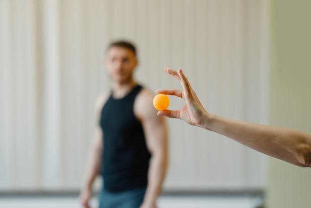Mão feminina segura a bola de pingue-pongue, homem em roupas esportivas no fundo, jogo de treinamento de tênis de mesa no ginásio.