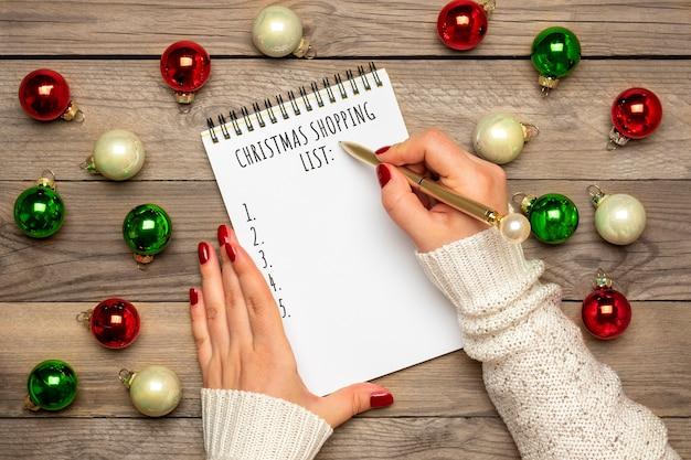 Mão feminina segura a caneta, escrevendo a lista de compras de natal, ideias para presentes no bloco de notas branco sobre fundo de madeira