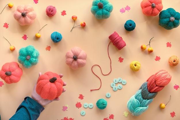Mão feminina segura abóbora de feltro laranja. materiais de artesanato para hobby. fundo de outono com várias abóboras de feltro diy