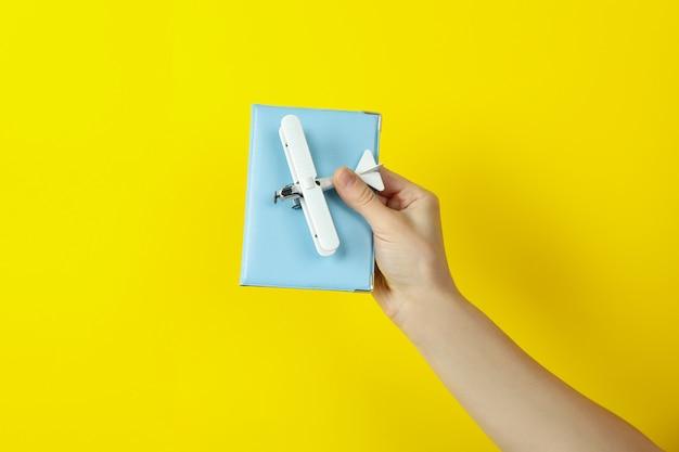 Mão feminina segura avião de brinquedo e passaporte em fundo amarelo