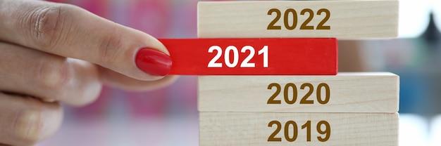 Mão feminina segura bloco de madeira vermelho com 2021 sinal closeup. pica e muda o conceito