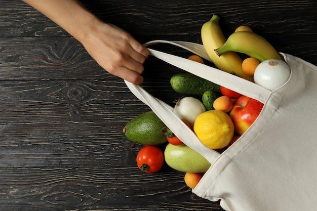 Mão feminina segura bolsa com legumes e frutas em fundo de madeira