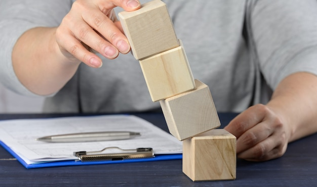 Mão feminina segura cubos caindo em cima da mesa. o conceito de crise de um gerente, mantendo a empresa à tona, estabilizando a empresa. desenvolvimento de estratégia de desenvolvimento