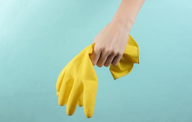 Mão feminina segura luvas amarelas para limpeza em fundo azul. conceito de limpeza doméstica