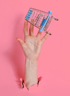 Mão feminina segura mini carrinho de compras através de papel rosa rasgado. conceito de compras minimalista