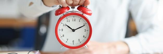 Mão feminina segura o despertador vermelho na mesa de trabalho. conceito de gerenciamento de tempo e prazos