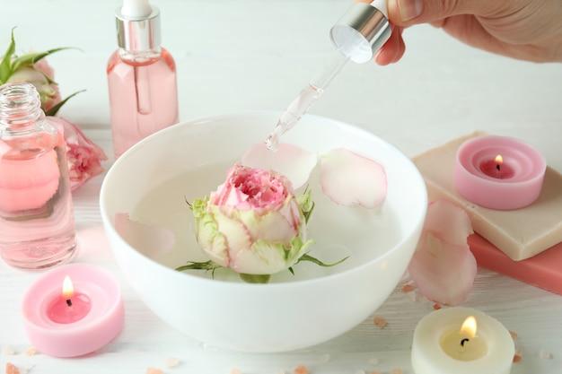 Mão feminina segura pipeta com óleo essencial de rosa, close-up
