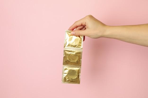 Mão feminina segura preservativos em fundo rosa, espaço para texto