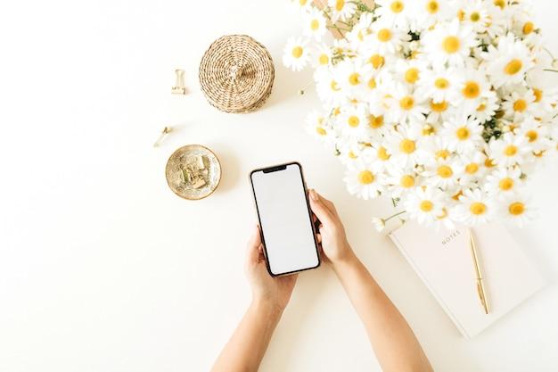 Mão feminina segura smartphone com tela em branco. espaço de trabalho de mesa de escritório em casa com buquê de flores de margarida de camomila e caderno em fundo branco.