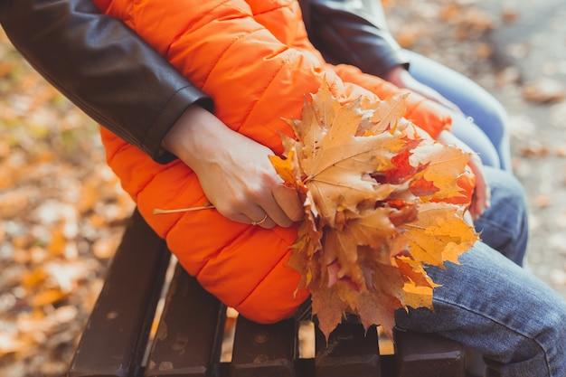Mão feminina segura um buquê de folhas de bordo de outono. conceito de temporada e natureza de outono.