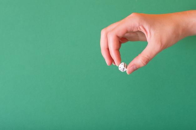Mão feminina segura um dado branco sobre um fundo verde. idéia para jogos de azar, cassino, dados.
