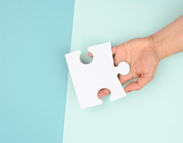 Mão feminina segura um fragmento de um grande quebra-cabeça branco sobre um fundo azul, o conceito de encontrar uma ideia, resolver um problema